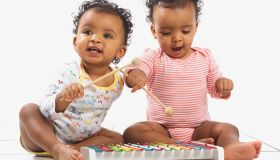 Twin girl and boy playing with xylophone, 18 months