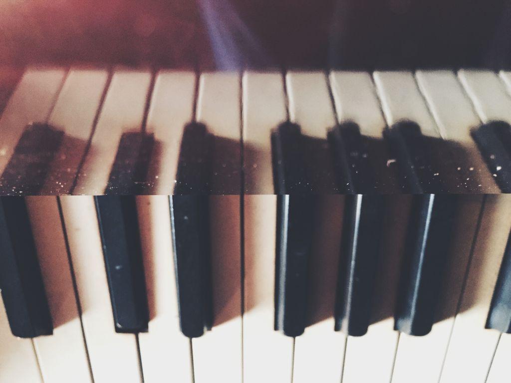 Close-Up Of Piano Keys Reflecting On Metal