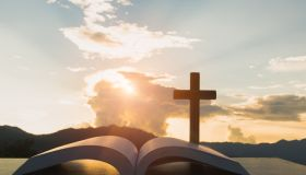 Close-Up Of Bible With Cross Against Sky During Sunset