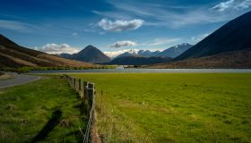 Landscape of mountains, road, grass field with Lake Pearson on a sunny day with blue sky in New Zealand